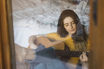 Portrait of relaxed young woman sitting behind windowpane playing guitar