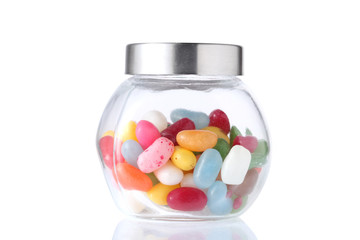 a glass jar half  full of colored candies with isolated on white background with clipping path