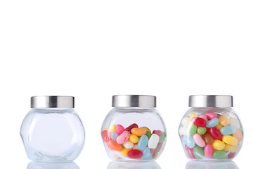 therre glass jar, one empety, one half empty and one full of colored candies isolated on white background with clipping path and copy space for your text