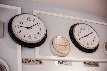international clock with different time zone for New York, Paris and Bangkok are hang on the wall
