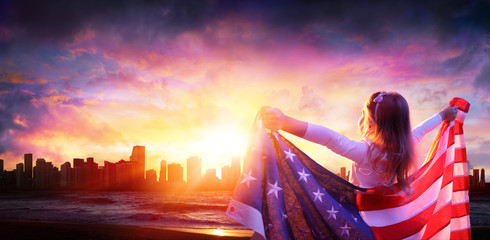 Little Girl In Freedom With American Flag - City At Sunset