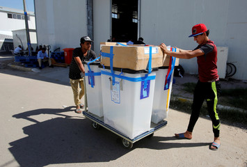 Workers of the Iraqi Independent High Electoral Commission move ballot boxes outside a warehouse in Baghdad