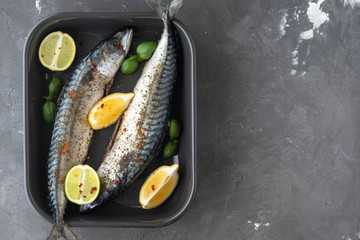 Two fresh mackerels in a black ceramic bowl with condiments. Upper plane.