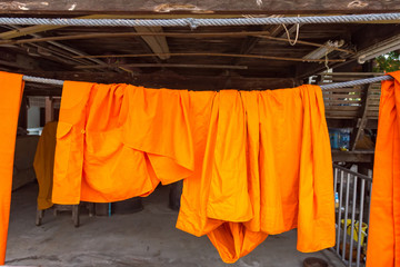 Orange and saffron robes of Buddhist monks hanging on wooden.Thailand.