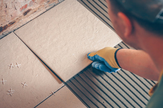 The worker carries out installation of a tile on a floor, finishing and facing works