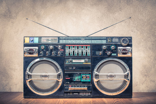 Retro design ghetto blaster stereo radio cassette tape recorders boombox from circa 80s front concrete wall background. Vintage instagram old style filtered photo