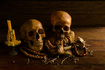 Two skulls and candle on wooden background, still life.