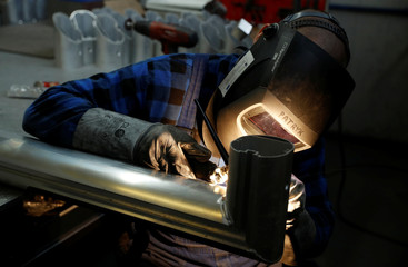 A worker welds the aluminium part of a goal at at Interplastic, a Polish manufacturing company who are supplying the football goalposts for the 2018 World Cup finals in Russia, in Chwaszczyno