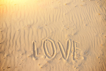 big text LOVE in the sand of the beach