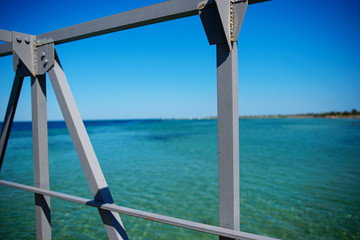 Swimming ladder from stainless steel for descent into sea water on pier. Silent bay ideal for children swim and play