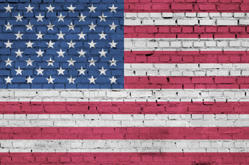 United States of America flag is painted onto an old brick wall