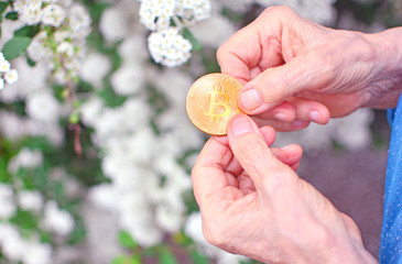 Concept of pension of future. Elderly woman holds a bitcoin coin symbol in wrinkled hands.
