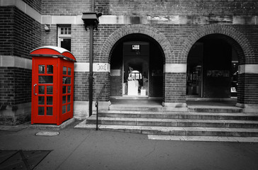 Black and white street scene with selective color on a red phone box in Sydney, Australia