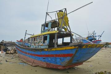 An old abandoned fishing boat in Mui Ne Fishing Village, Binh Thuan Province, Vietnam