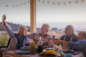 group of adults friends elderly retired having fun taking a picture like selfie all together during a dinner outdoor on the terrace rooftop. celebrate with meal and wine and send memories