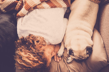 best friends forever with nice pug dog and beautiful swirl hair caucasian woman sleep together in the morning on the sofa. absolute friendship concept between people and animals. tenderness  story
