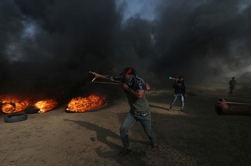 Demonstrator uses a slingshot to hurl stones during a protest where Palestinians demand the right to return to their homeland, at the Israel-Gaza border, in the southern Gaza Strip