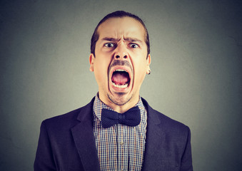young angry man screaming with wide open mouth