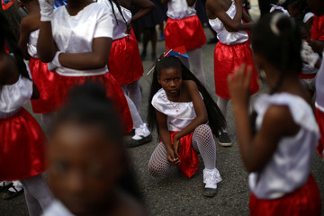 A girl rests before celebrations for National Haitian Flag Day in the streets of Petion Ville, Port-au-Prince