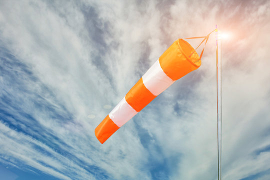 red and white wind sock on blue sky and clouds background