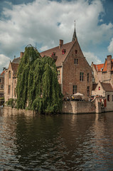 Wall Murals Bridges Leafy tree with old brick buildings on the canal's edge in a sunny day at Bruges. With many canals and old buildings, this graceful town is a World Heritage Site of Unesco. Northwestern Belgium.