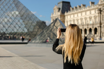Girl standing near Louvre and glass pyramind in black dress in Paris, talking photo by smartphone. Concept of fashion and trip to Franse, European landmarks.