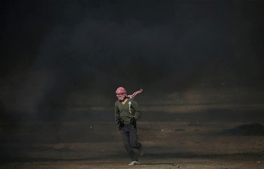 Demonstrator runs during a protest where Palestinians demand the right to return to their homeland, at the Israel-Gaza border, in the southern Gaza Strip