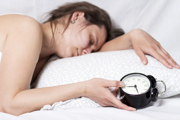 Sleepy girl can not wake up from the alarm bell. A woman is sleeping in bed and holding an alarm clock in her hand. girl can not get out of bed early in the morning. Lack of sleep concept