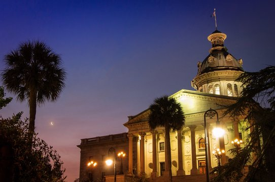 South Carolina Capital Building at sunrise with crescent moon and palmetto trees