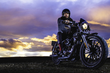 Modern biker sits and ready for shooting on classic motorcycle at closed road. Outdoor portrait and urban lifestyle