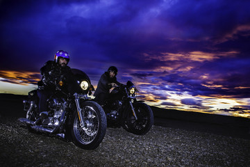 Modern bikers ride on a closed road on classic motorcycle at sunset. Outdoor portrait and urban lifestyle