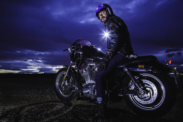 Modern biker turns on classic motorcycle at sunset with flash at back. Outdoor portrait and urban lifestyle