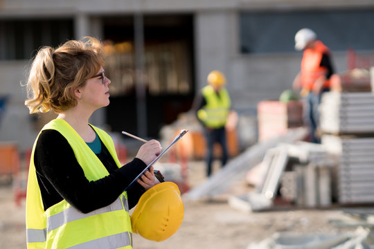 Young female civil engineer at work on construction site