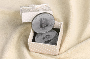 The silver bitcoin lies in a small orange gift box with a small bow on a blanket made of soft and fluffy light orange fleece fabric with a large number of relief folds