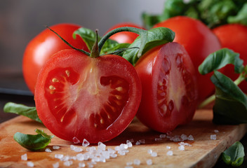 Red tomatoes with green basil on wooden table.