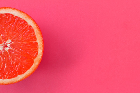 Top view of an one grapefruit slice on bright background in pink color. A saturated citrus texture image