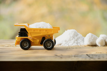 A small yellow toy truck is loaded with a stone of white salt next to a pile of salt. A car on a wooden surface against a background of autumn forest. Extraction and transportation of salt