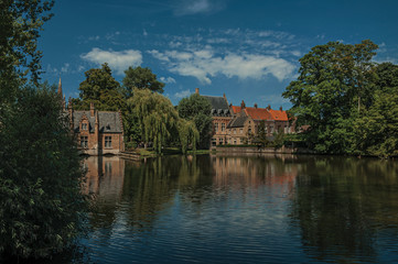Amazing lake surrounded by greenery and old brick building on the other side in Bruges. With many canals and old buildings, this graceful town is a World Heritage Site of Unesco. Northwestern Belgium.