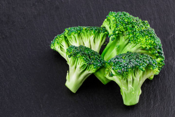 Fresh broccoli on a black slate, top view with space for text