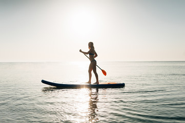 Stand up paddle board woman paddleboarding on Hawaii standing happy on paddleboard on blue water.