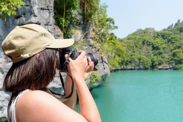 Woman tourist at Thale Nai on Koh Mae Ko island viewpoint use camera taking photos at beautiful nature landscape of Blue Lagoon (Emerald Lake) in Mu Ko Ang Thong National Park, Surat Thani, Thailand
