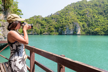 Woman tourist at Thale Nai on Koh Mae Ko island viewpoint use camera taking photos at beautiful nature landscape of Blue Lagoon (Emerald Lake) in Mu Ko Ang Thong National Park, Surat Thani, Thailand
