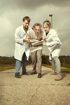 Two older retro paramedic freak hunters in medical coats catching crazy man in park