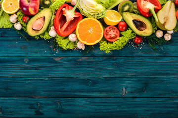 Assortment of fresh vegetables and fruits. Healthy food On a blue wooden background. Top view. Copy space.