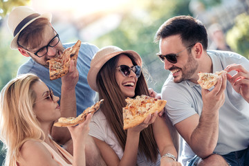 Close up of four young cheerful people eating pizza