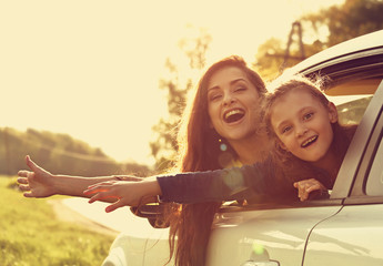 Happy traveling laughing mother and kid girl looking from the new car window on the beautiful nature background. Good purchase of vehicle. Toned closeup portrait