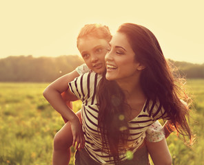 Smiling kid girl laughing on the happy enjoying mother back on sunset bright summer background. Closeup toned vintage portrait of happiness.
