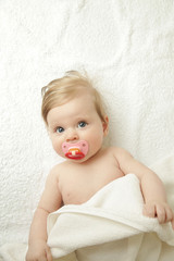 Adoabre newborn with pacifier looking at camera