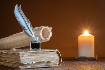 Quill pen by candle light with old paper and books