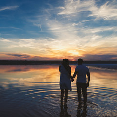 Portrait, silhouette of happy couple watching the colourful bright sunset standing in large lake, reflection in the water, holding hands